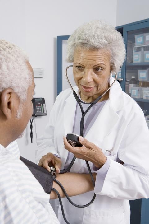 Senior Medical Practitioner Taking Blood Pressure for Senior Male Patient